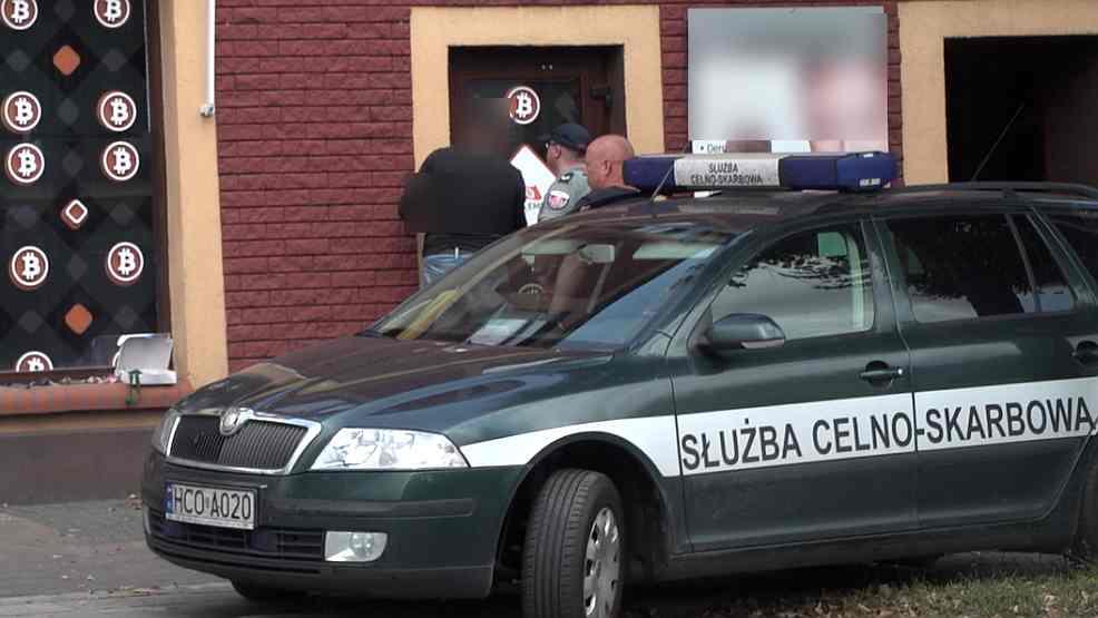 Funkcjonariusze  Krajowej Administracji Skarbowej forsują drzwi Bitcoin Embassy w Jarocinie  - Zdjęcie główne
